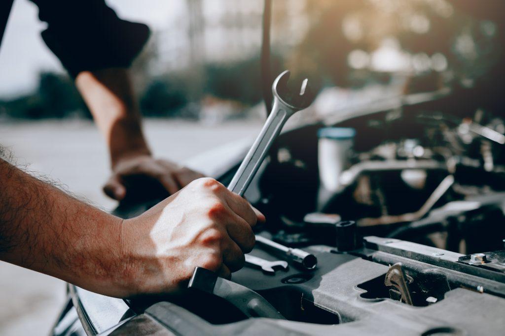 Le mécanicien automobile tient une clé prête à vérifier le moteur et l'entretien.